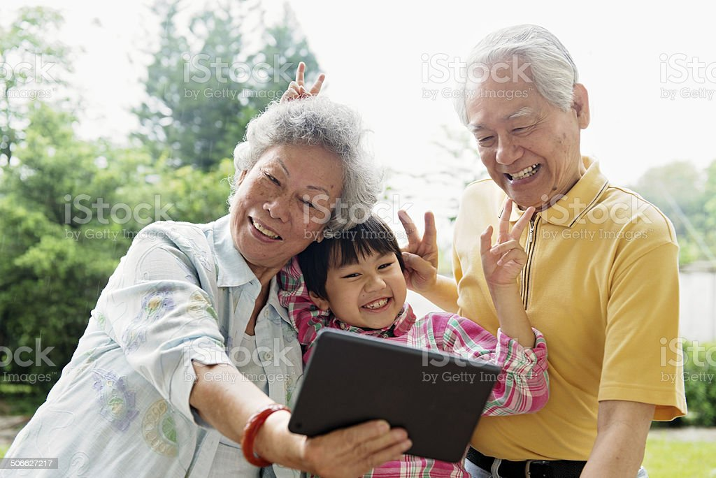 Grandson and grandparents taking selfie with digital tablet stock photo
