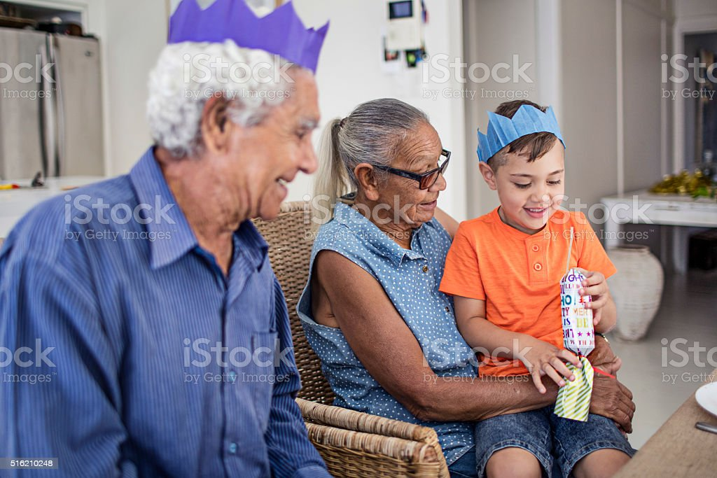 Grandson checking Christmas cracker at table after pulling it stock photo