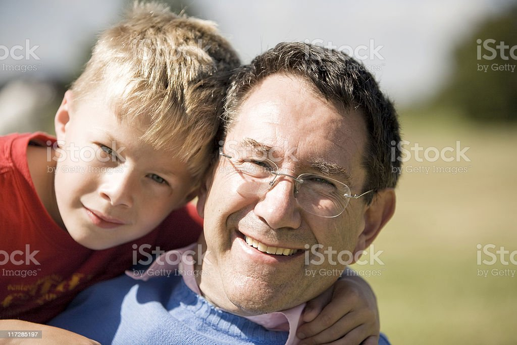 grandson cuddling a young looking grandfather royalty-free stock photo