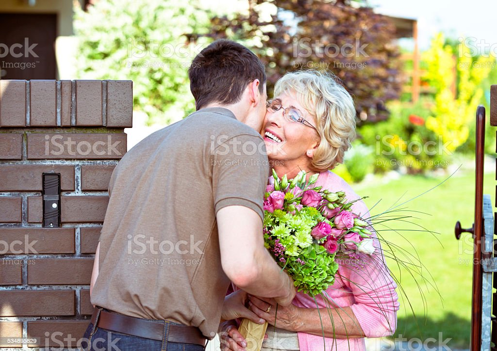 Grandson giving flowers to his grandmother Outdoor picture of grandson giving flowers to his happy grandmother. 2015 Stock Photo
