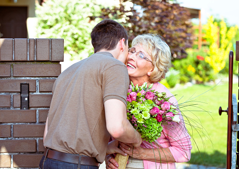 Grandson Giving Flowers To His Grandmother Stock Photo - Download Image Now