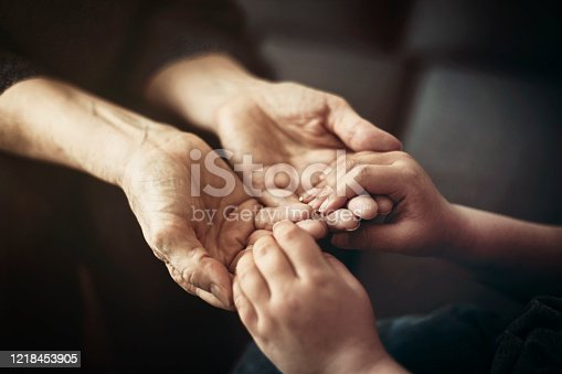 istock Grandson holding grandmother hands close up view 1218453905