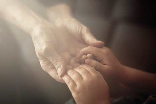 Grandson holding grandmother hands close up view
