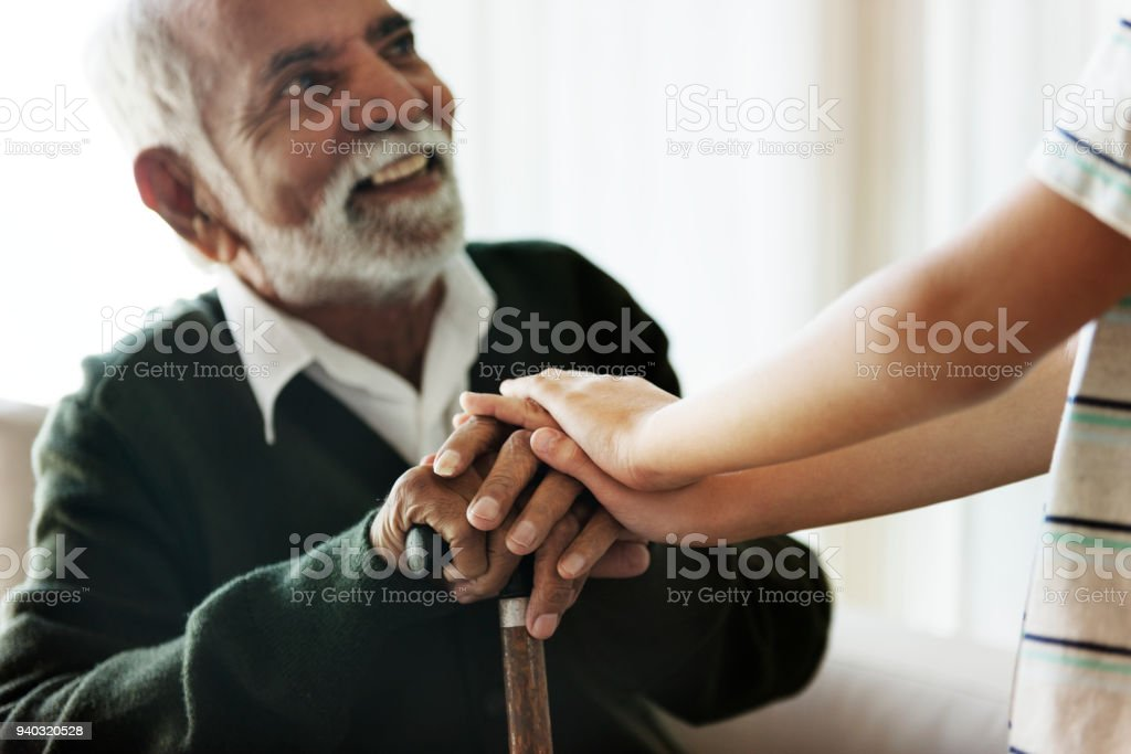 Grandson holding grandpa's hands stock photo