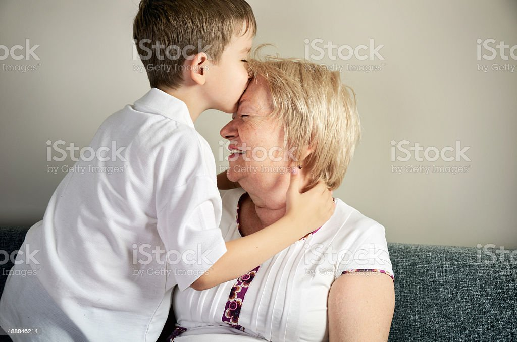 grandson kissing his grandmother stock photo