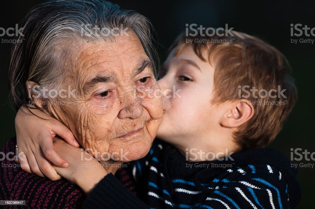 Grandson kissing his great grandmother against black background royalty-free stock photo