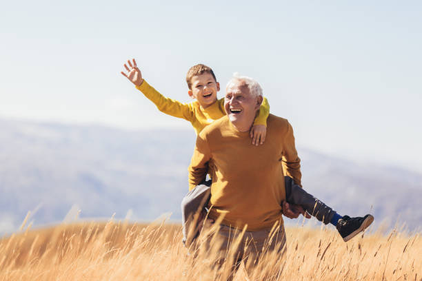 Grandson piggyback with his grandfather in autumn. stock photo