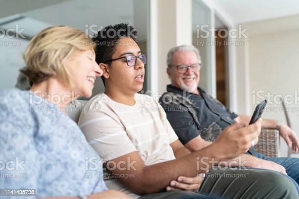 Grandson showing smarphone to grandparents