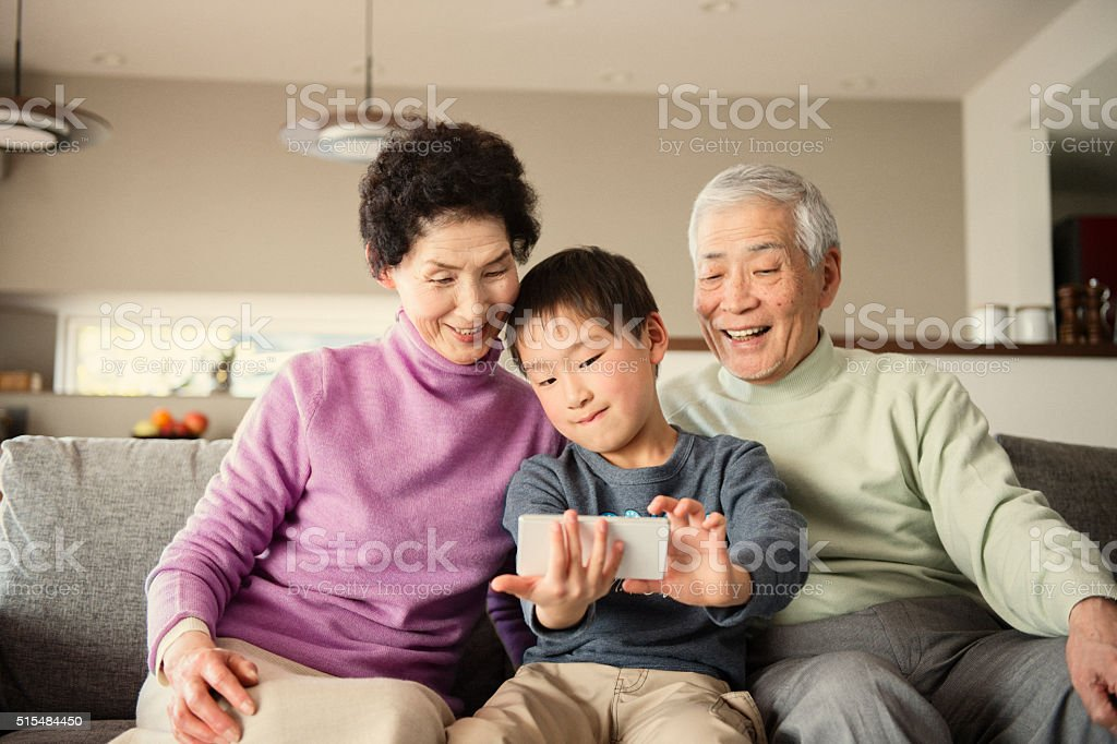 Grandson taking a family photo with smartphone stock photo