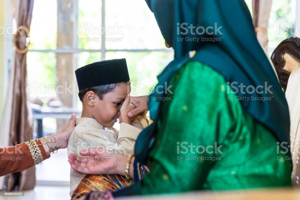 Nieto teniendo bendiciones durante el festival de hari raya en Malasia - foto de stock