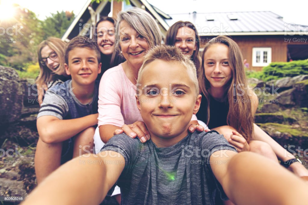 Grandson taking selfie of his grandmother and cousins stock photo