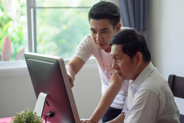 Grandson teaching grandfather how to Using computer and technology in home . young Teacher help senior Man learning to connect internet stock photo