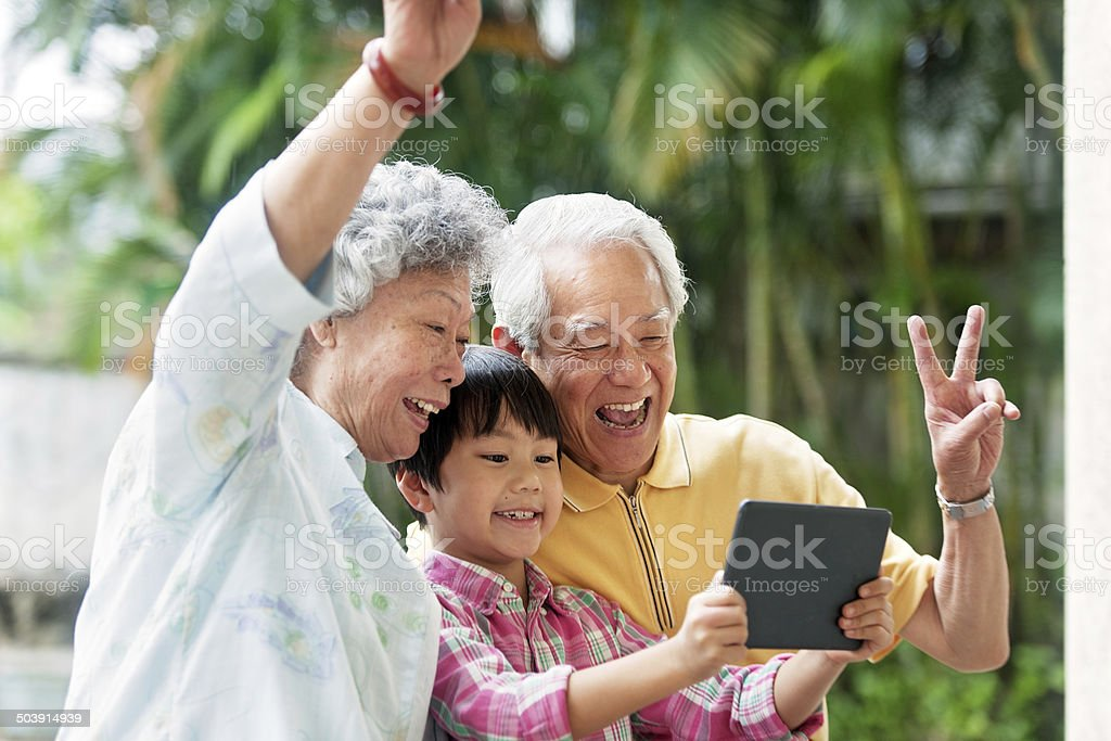 Grandson teaching grandparents how to use a digital tablet stock photo