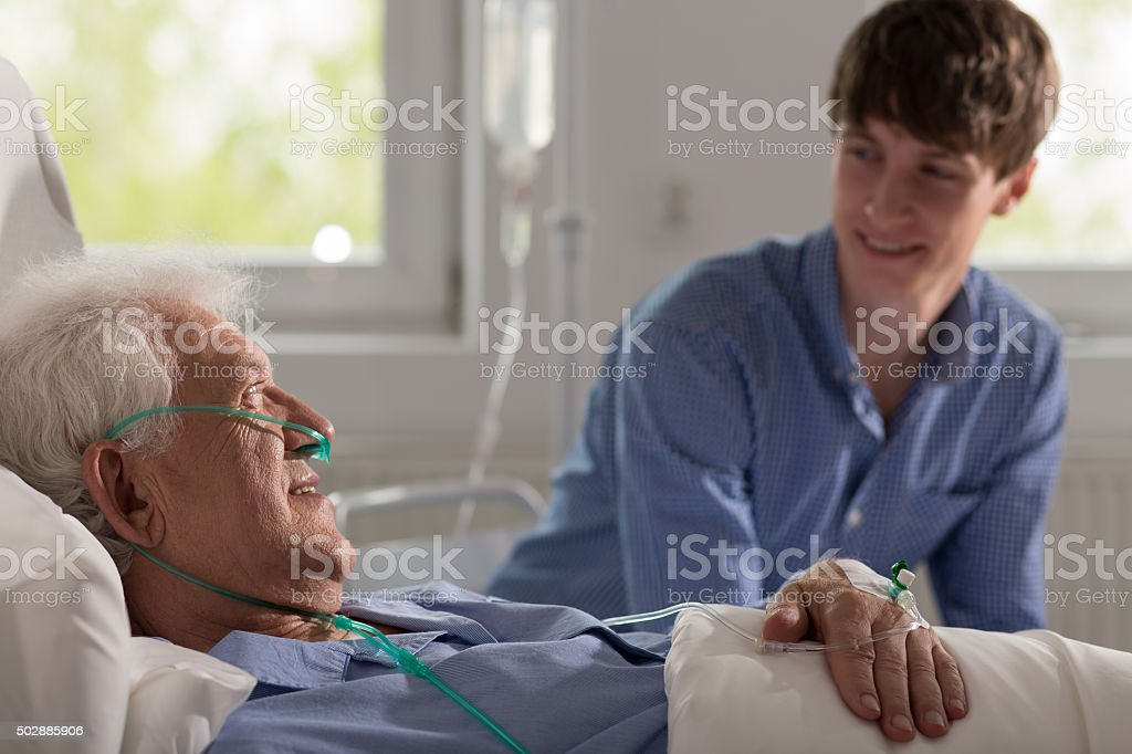 Grandson visiting ill grandfather stock photo
