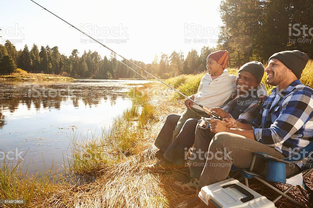 Grandson With Father And Grandfather Fishing By Lake stock photo