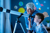 Grandfather teaching grandson using telescope to see planets and galaxy. Child watching stars through a telescope at night with senior man. Grandpa and grandchild looking together at their positive future: growing, investment and vision concept.