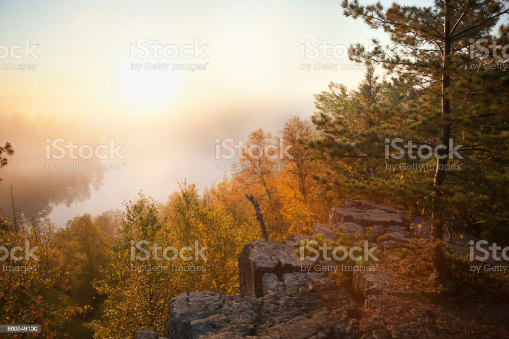 Granite cliff and pines overlooking misty lake in northern Minnesota boundary waters at sunrise during autumn stock photo