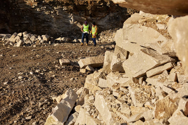 Granite Mining Worksite Wide angle shot of two industrial  workers wearing reflective jackets, one of them African, walking on mining worksite outdoors, focus on pile of rocks in foreground, copy space frontier field stock pictures, royalty-free photos & images