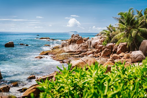 Granite rocky coastline on tropical La Digue island, Seychelles. Beautiful palm trees, boulders and pacific ocean.
