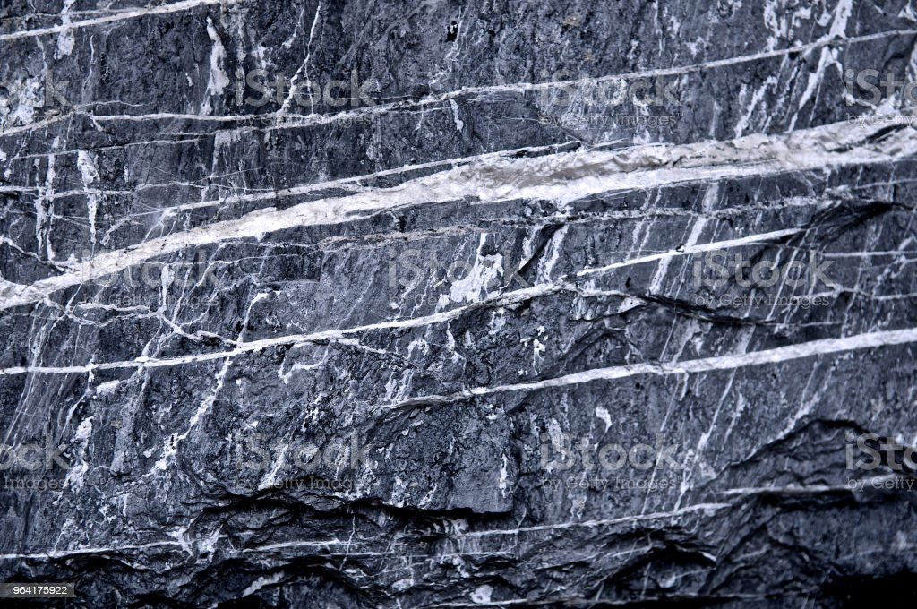 Granite stone scratched wall background grunge texture rough. Abstract construction concrete stone wall. Mountain rock or volcano stone. Cool and chic adventure wallpaper. Black and white color. Close up. stock photo