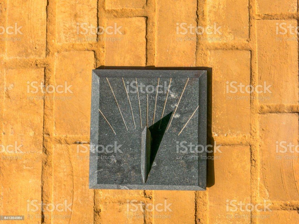 Granite Sundial - sun clock on orange brick floor stock photo