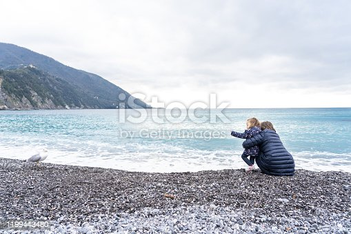 Granmother and granddaughter on the beach in winter, Camogli in