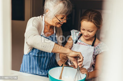 istock Granny and kid cooking in kitchen 1165772730