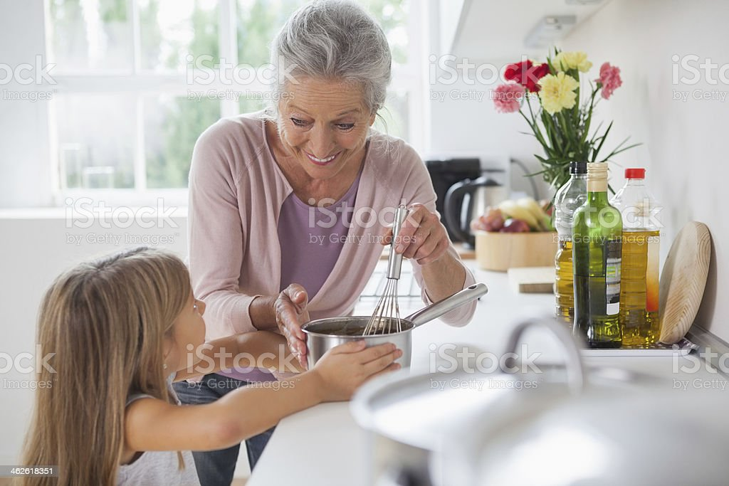 Granny and little girl making chocolate sauce together royalty-free stock photo