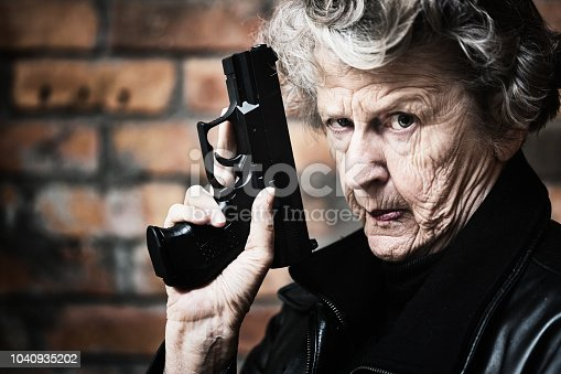 A wrinkled old woman glares at camera as she holds up her gun against a brick wall. She's prepared.