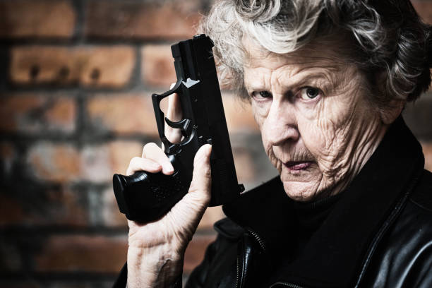 granny get your gun! fierce old woman holds pistol - female spy stock photos and pictures