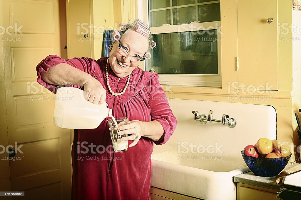 Granny in Kitchen Pouring Milk stock photo