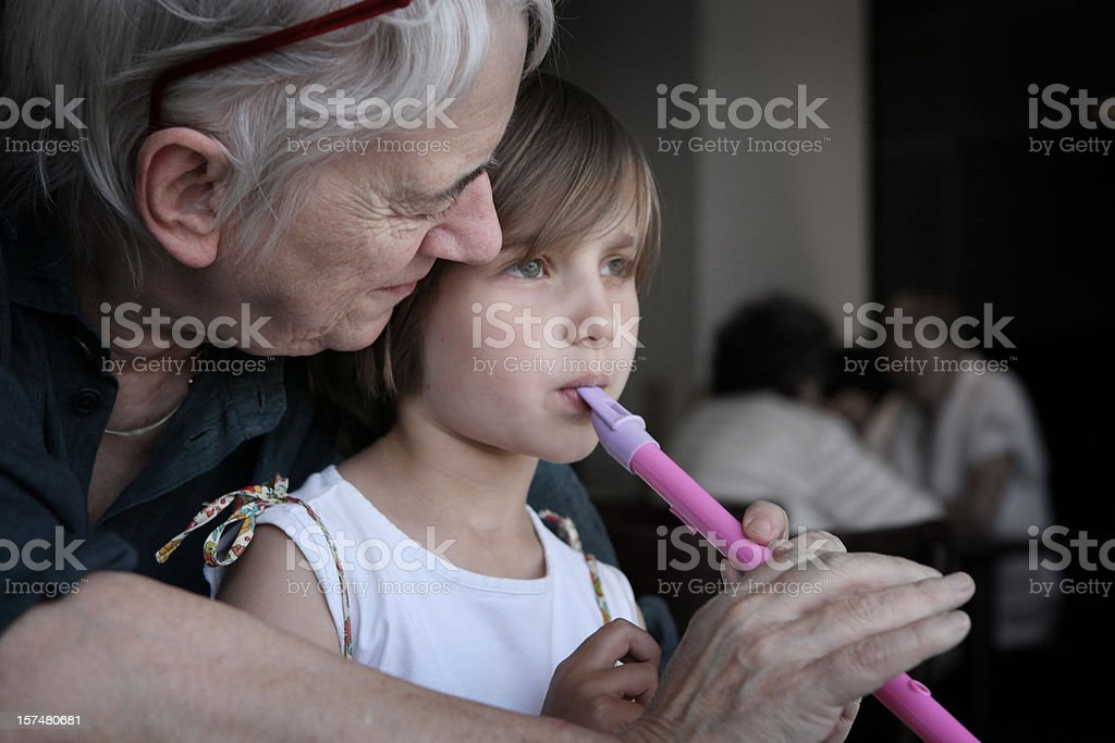 Granny learning girl to play flute royalty-free stock photo