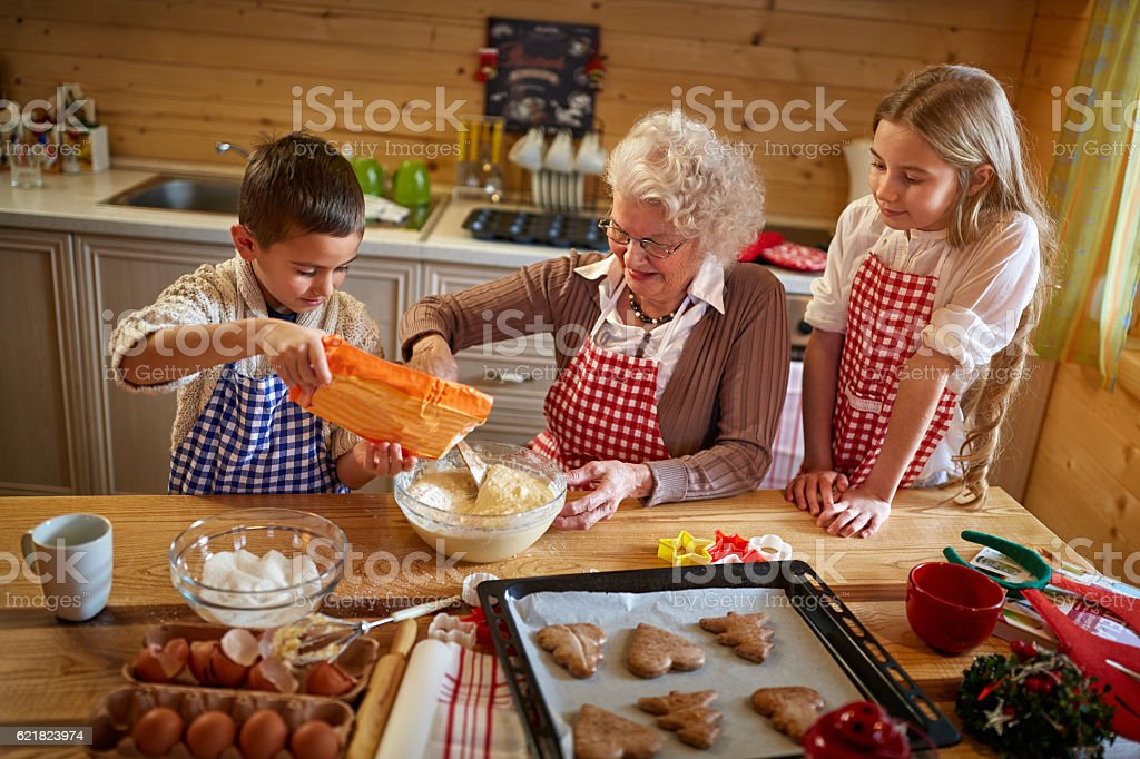 granny making Christmas cookies with kids stock photo