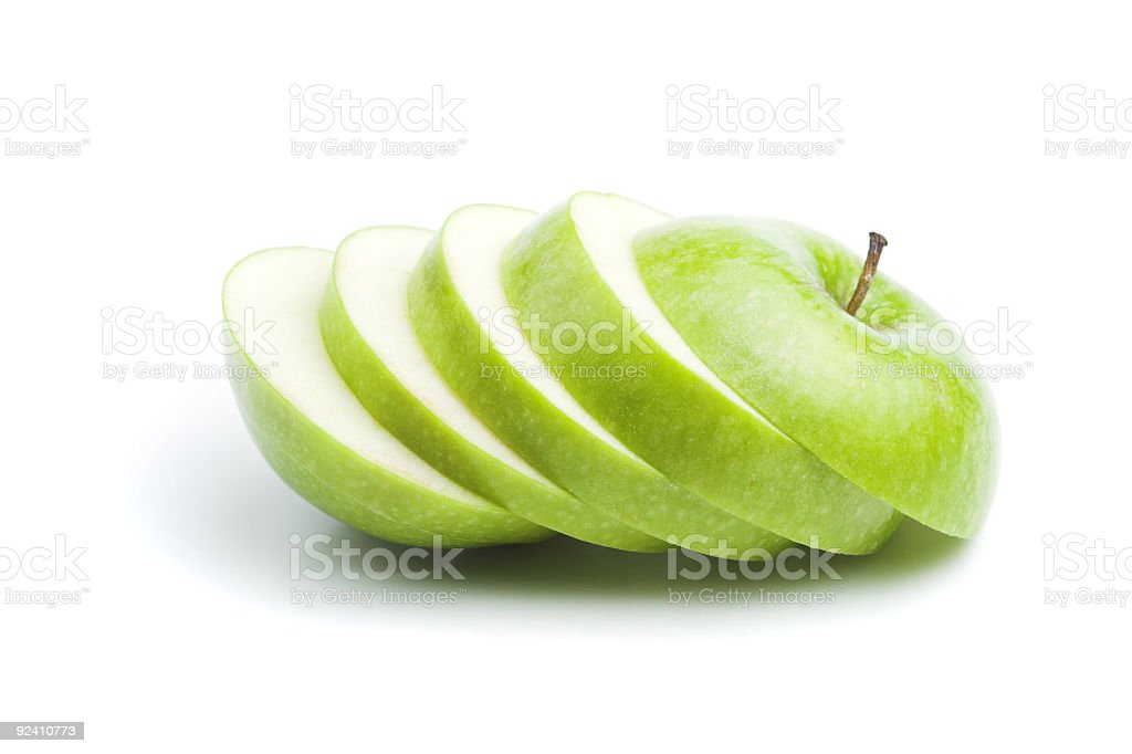 A Granny Smith apple sliced and arranged artistically royalty-free stock photo