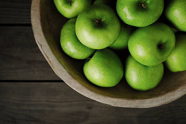 Granny smith apples in a big wooden bowl stock photo