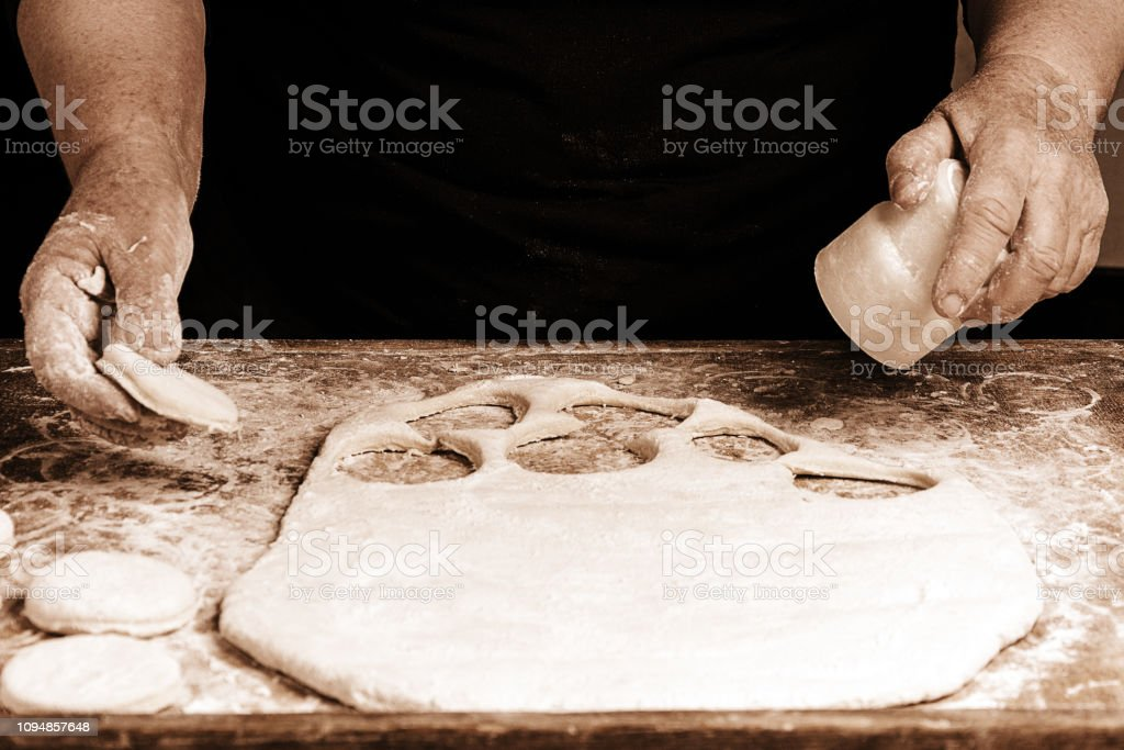 Granny squeezes a glass of a circle in a dough on the table 2018