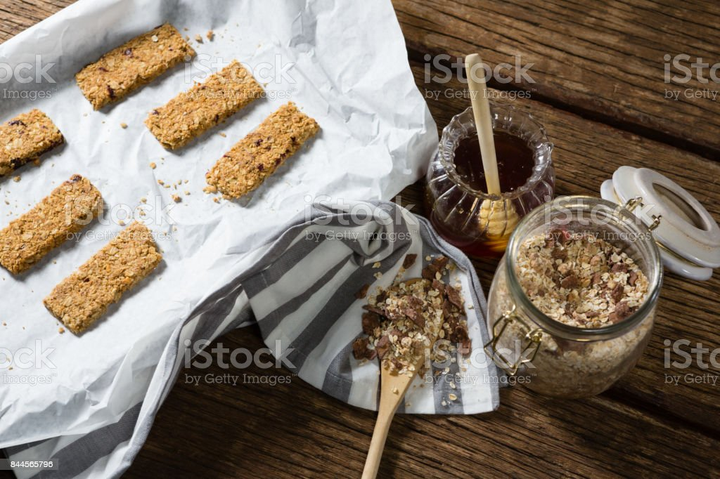 Granola bar and honey on wooden table stock photo