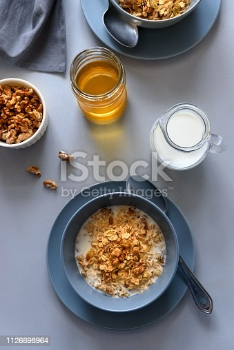 599887760 istock photo Granola bowl (oatmeal porridge) with blueberry, honey and milk on gray table. Flat lay. Selective focus. Healthy vegetarian food 1126698964