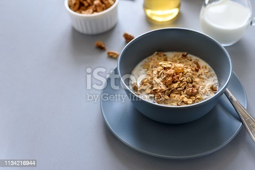 599887760istockphoto Granola bowl (oatmeal porridge) with blueberry, honey and milk on gray table. Flat lay. Selective focus. Healthy vegetarian food 1134216944