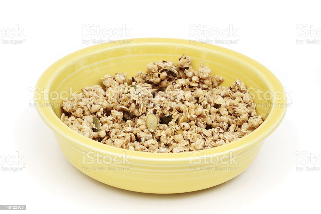 Granola cereal with flax and pumpkin seeds in a yellow stock photo