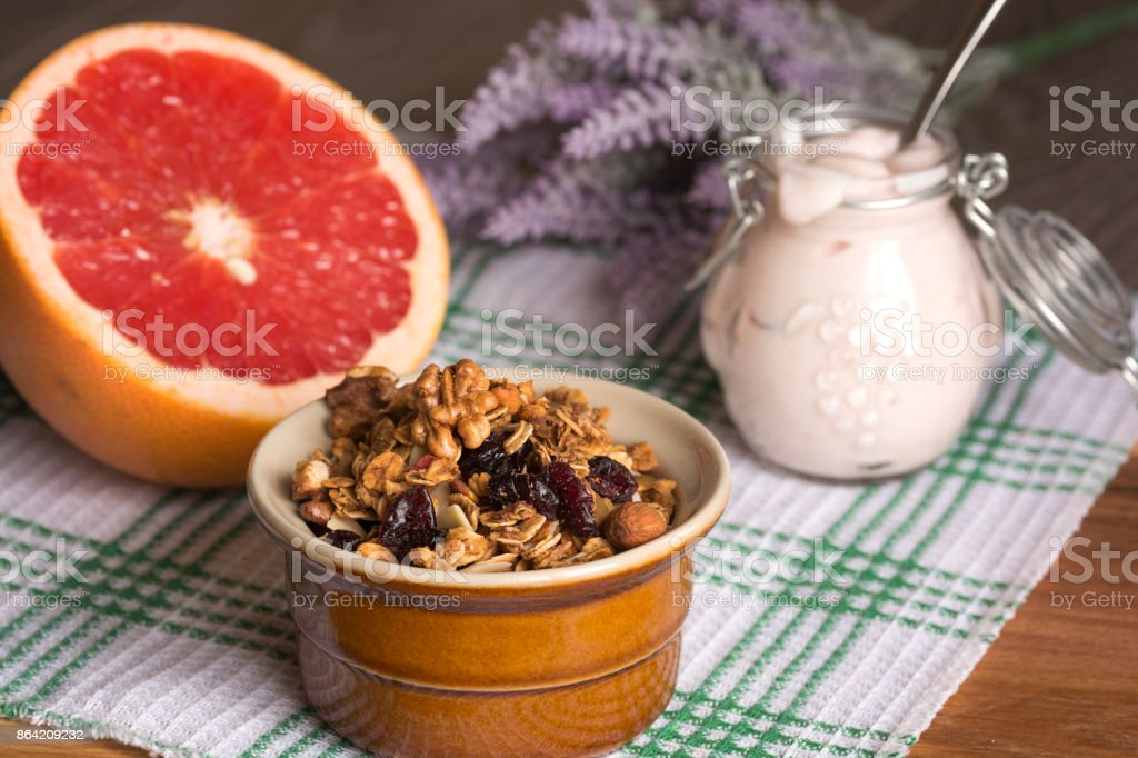 Granola from several types of cereals with nuts, coconut shavings and dried cranberries. Jar with homemade yogurt and grapefruit royalty-free stock photo