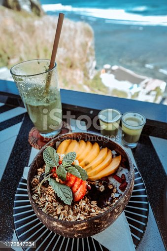 Granola fruit yogurt for healthy breakfast with sea view
