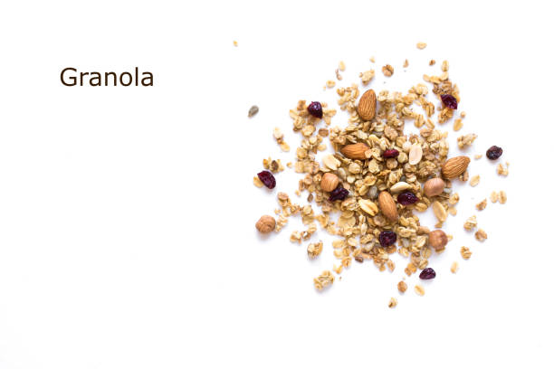 Granola Granola creative layout isolated on white background, copy space. Healthy snack or breakfast concept - homemade granola with grains, dry cranberries and nuts. nut food stock pictures, royalty-free photos & images