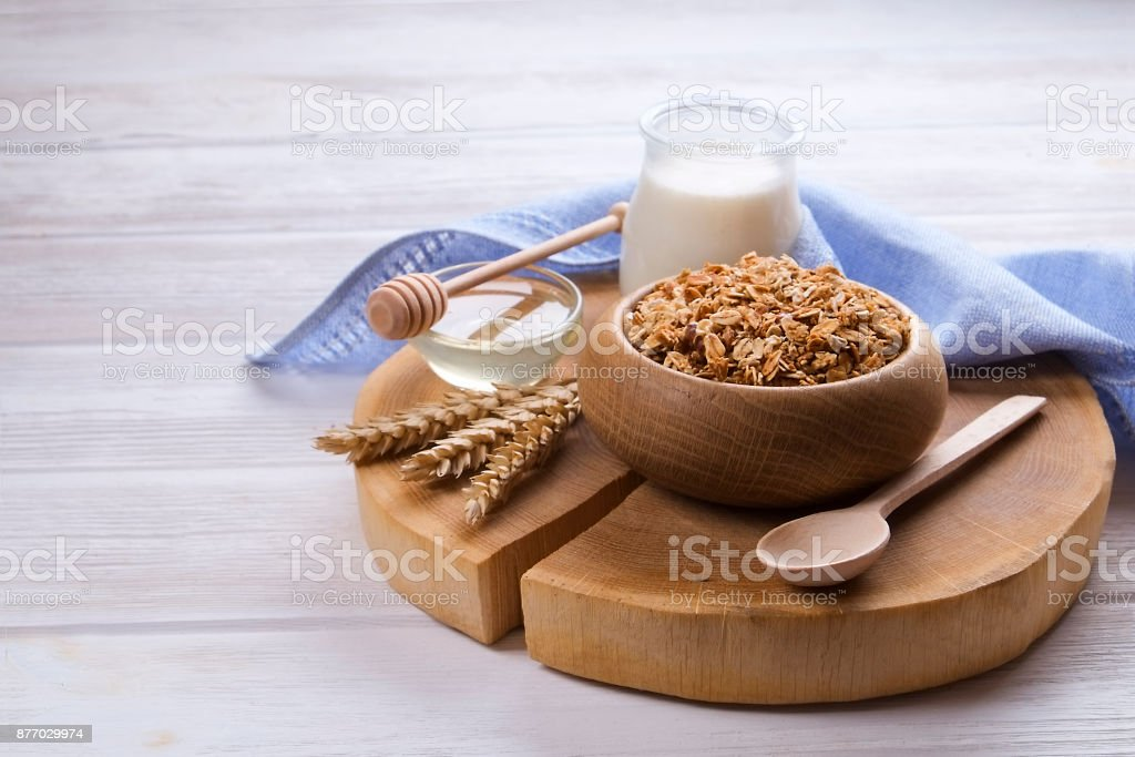 Granola superfood with almond and cashew nuts, dry fruits, raisins cherry in the wooden bawl on the white wood table, top view, bright light stock photo