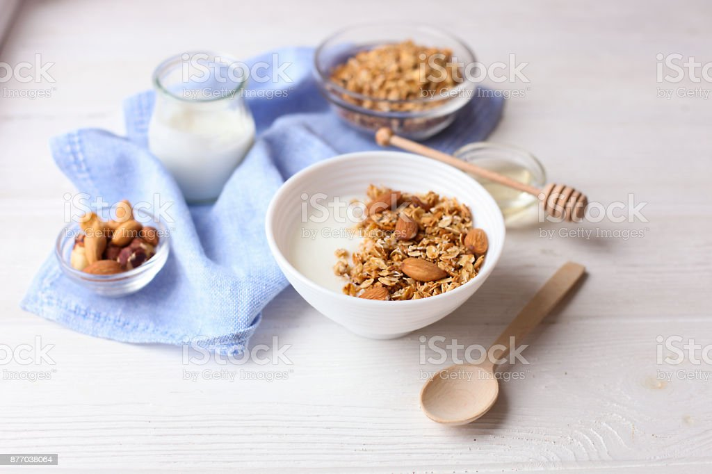 Granola superfood with almond and cashew nuts, dry fruits, raisins cherry in the ceramic bawl with milk and greek yogurt on the white wood table, top view stock photo