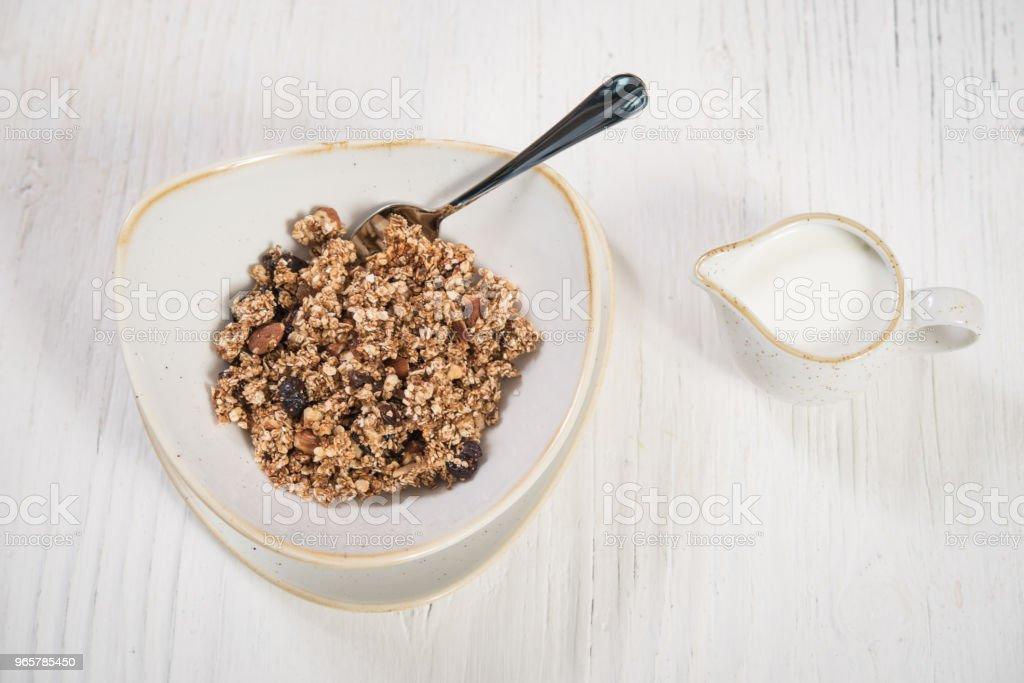 Granola med spannmål och nötter i plattan med mjölk - Royaltyfri Bord Bildbanksbilder