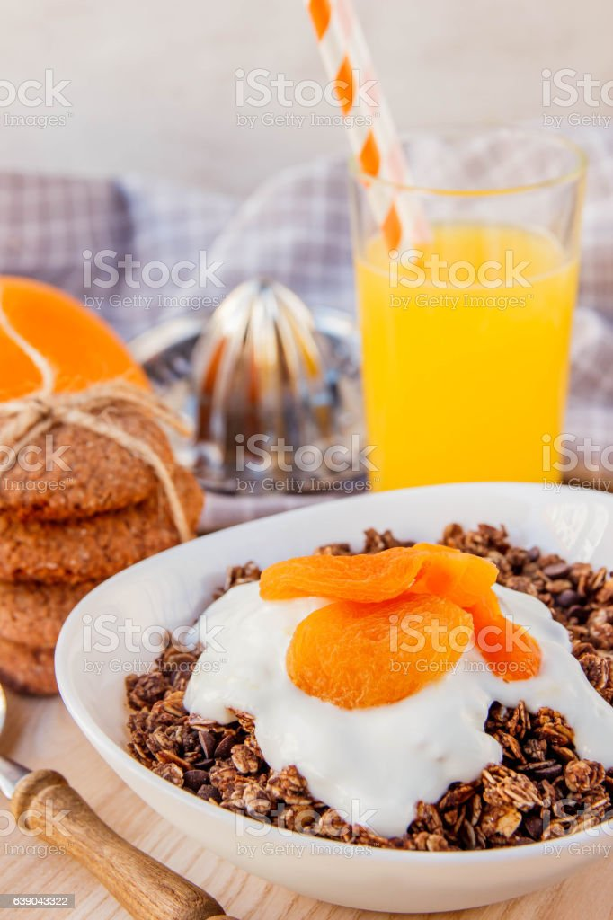 Granola with dried apricots and yogurt in the white bowl. stock photo