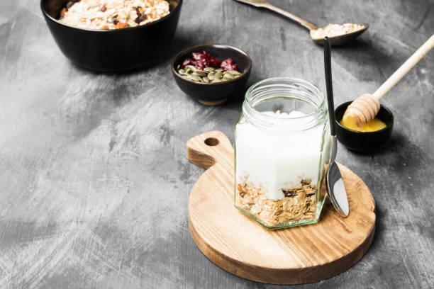 müsli mit joghurt, honig, nüssen, obst auf einem dunklen hintergrund. kopieren sie raum. essen-hintergrund - haferflocken rosinen stock-fotos und bilder