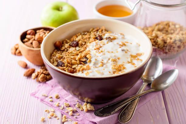 granola with yogurt in bowl on pink wooden background. - granola imagens e fotografias de stock