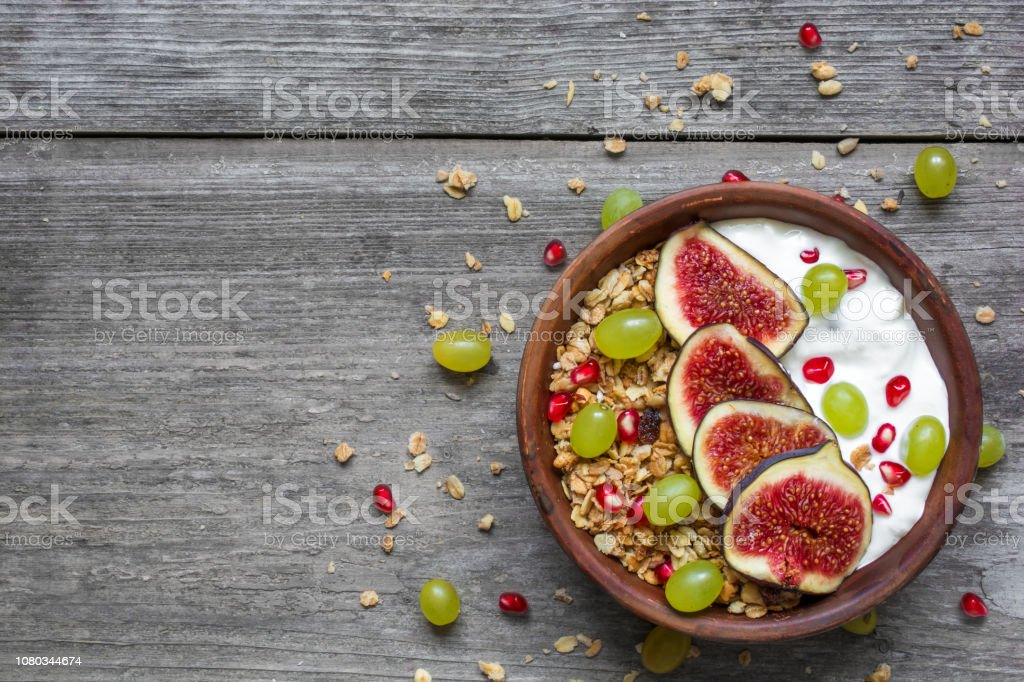 granola with yogurt, pomegranate seeds, figs, grape and nuts in a bowl on rustic wooden background